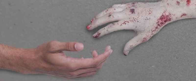 Zombie hand reaching out to healthy person for help