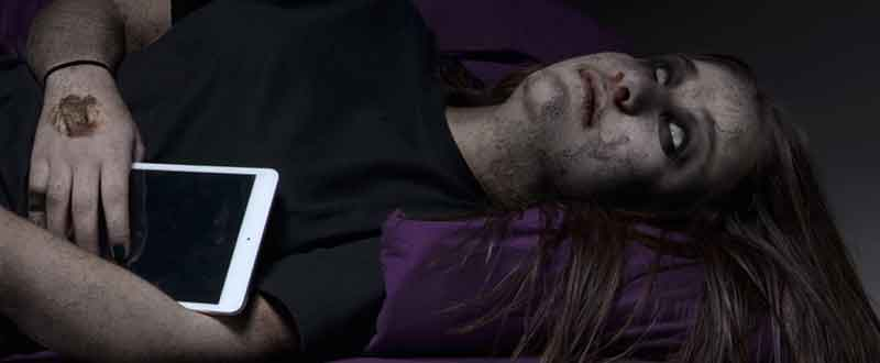 Zombie girl laying on the bed with ipad